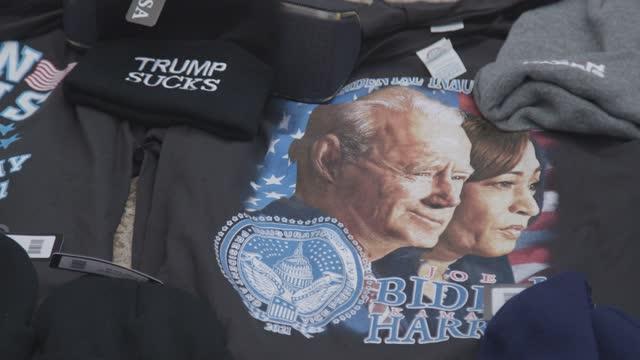 vendor sells t-shirts on independence avenue at the u.s. capitol on inauguration day on january 21, 2021 in washington, dc. joe biden was sworn in as... - 映像技法点の映像素材/bロール