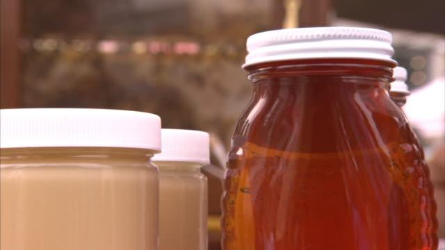 vídeos de stock, filmes e b-roll de a vendor sells wild honey at a farmer's market. - mel