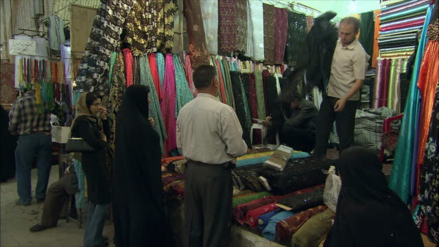 ms vendor showing textile to customers in bazaar, shiraz, iran - iran stock videos & royalty-free footage