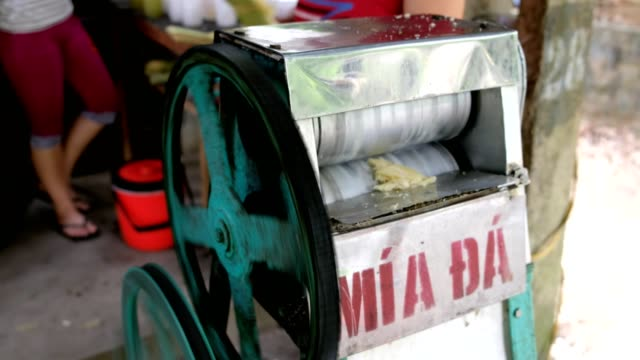 vendor squeezing crushed fresh sugar cane on machine - molasses stock videos and b-roll footage