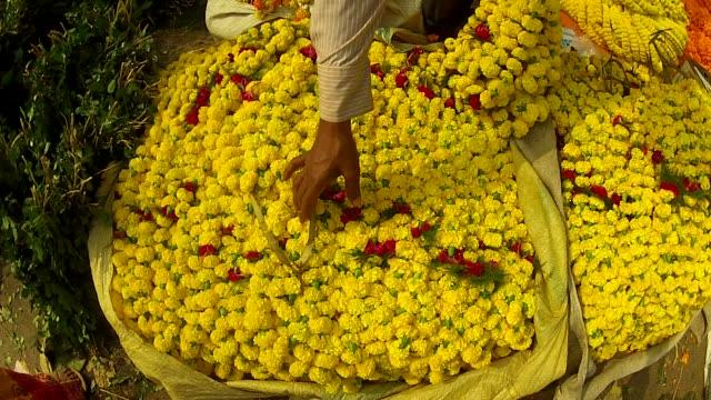 a vendor stacks yellow flower garlands at kolkata flower market. - kolkata stock videos & royalty-free footage