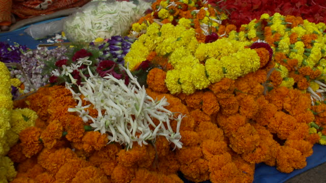 vídeos y material grabado en eventos de stock de a vendor stand displays orange and yellow flower garlands at a calcutta market. - calcuta