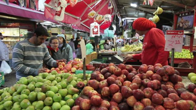 vídeos de stock, filmes e b-roll de a vendor stocks produce at a stand in the shuk ha'carmel. - israel
