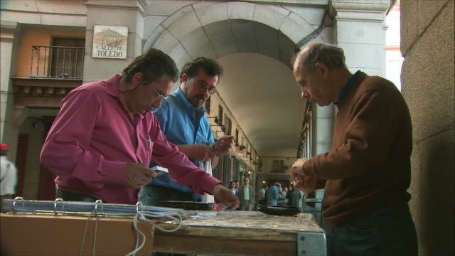 ms vendor talking to customers buying stamp and coins in market, plaza mayor, madrid, spain - flea market stock videos and b-roll footage