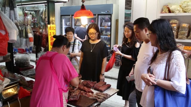 vídeos y material grabado en eventos de stock de a vendor trims a piece of ham at a meat store in the sheung wan district of hong kong china on thursday sept 29 a vendor cuts pieces of ham at a meat... - sheung wan
