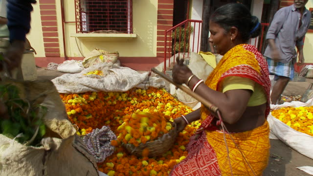 A vendor uses a basket to load flowers into a bag at an outdoor market in Calcutta.