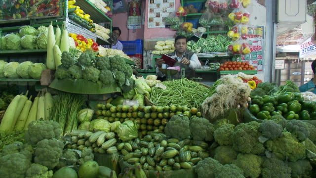 vídeos y material grabado en eventos de stock de a vendor waits for customers behind a display of green fruits and vegetables. - calcuta