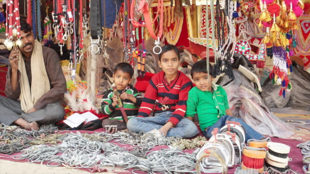 vendor with kids selling camel decorations at pushkar mela fair it comes alive with vibrant folk music and dances horse and camel races religious... - religious music stock videos and b-roll footage