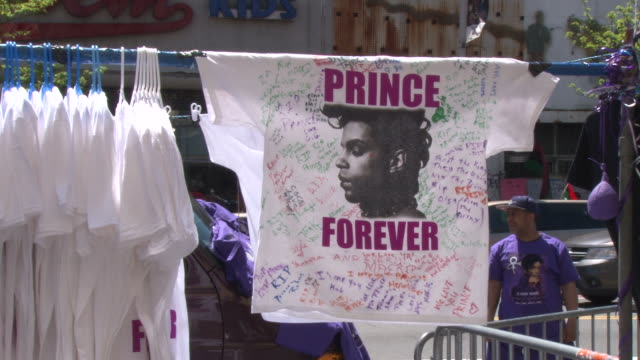 vidéos et rushes de vendors enthusiastically hack prince related merchandise as they try to capitalize on the memorial setting / items for sale include prince teeshirts... - vendeur ambulant