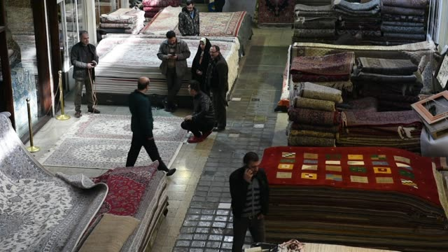Vendors measure Persian carpets for a customer in the rug bazaar in Tehran Iran on Monday Jan 15 2018