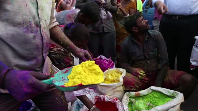 vendors prepare plastic bags of colored powder at a market stall ahead of holi celebrations in mumbai india on saturday march 11 a vendor ties a... - body adornment stock videos and b-roll footage