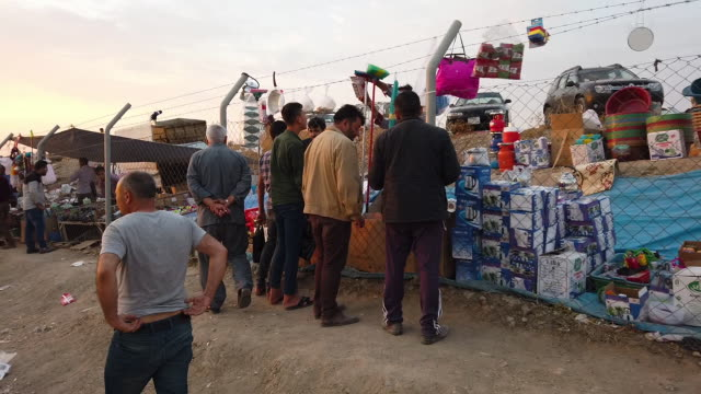 vendors selling fruits, vegetables, and cooking utilities hawk their wares to refugees outside of badarash idps camp which has continued to swell for... - iraq stock videos & royalty-free footage