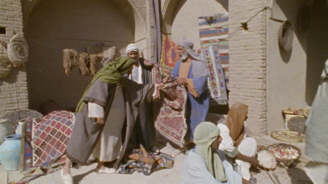 ws recreation vendors selling produce, rugs and pottery at middle eastern market / iran  - historische nachstellung stock-videos und b-roll-filmmaterial