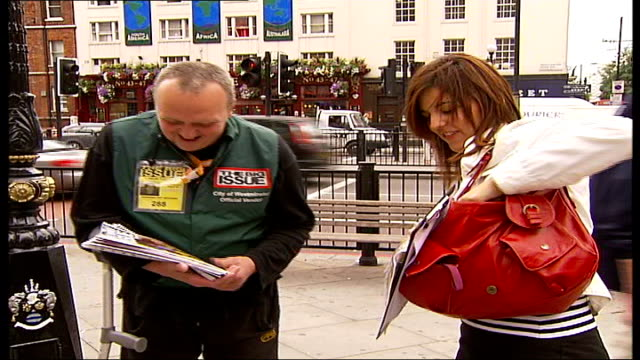 vidéos et rushes de vendors selling 'the big issue' england london ext back view of 'big issue official vendor' selling copies on streey/ big issues vendor shouting... - vendeur ambulant