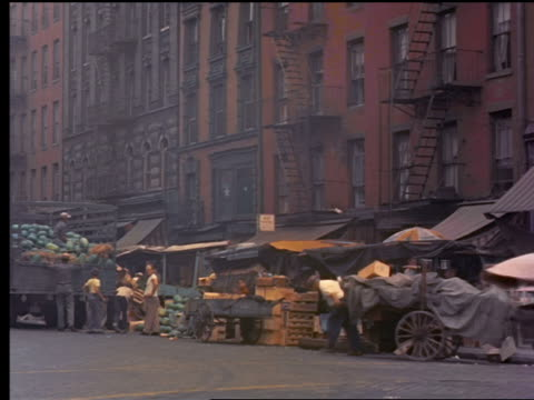 1955 vendors setting up carts on side of street in new york city / bus passes in foreground - 1955 stock videos & royalty-free footage