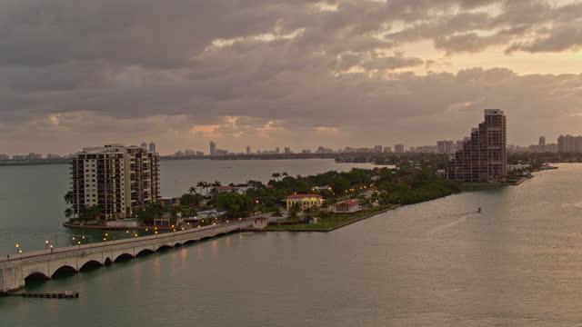 stockvideo's en b-roll-footage met venetiaanse causeway bridge en biscayne island, miami, florida, bij zonsopgang. luchtvideo met achterwaartse camerabeweging. - venetian causeway bridge