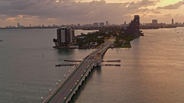 stockvideo's en b-roll-footage met venetiaanse causeway bridge en biscayne island, miami, florida, bij zonsopgang. luchtvideo met forwarding-panning camerabeweging. - venetian causeway bridge