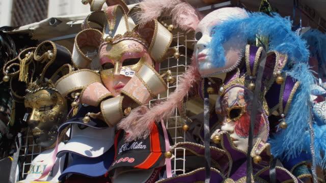 cu, pan, venetian masks on market stall, venice, italy - mellanstor grupp av objekt bildbanksvideor och videomaterial från bakom kulisserna