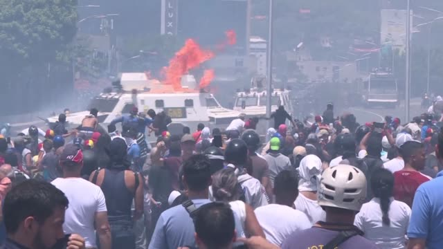 venezuelan opposition demonstrators throw cocktail molotovs at national guard tanks during violent clashes after an attempted coup in caracas - venezuela stock videos & royalty-free footage