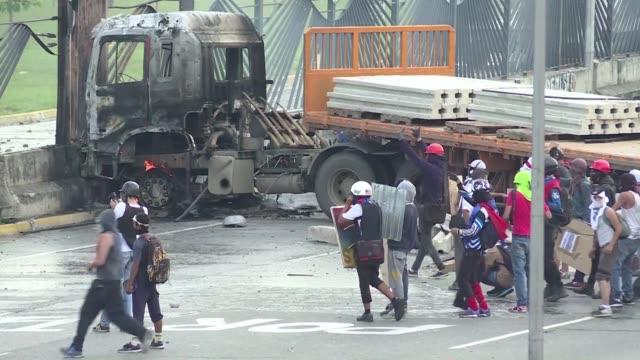 vídeos y material grabado en eventos de stock de venezuelan protestors burned lorries and faced tear gas and water cannons as they massed on streets in caracas in protest over the death of a young... - artículo de emergencia