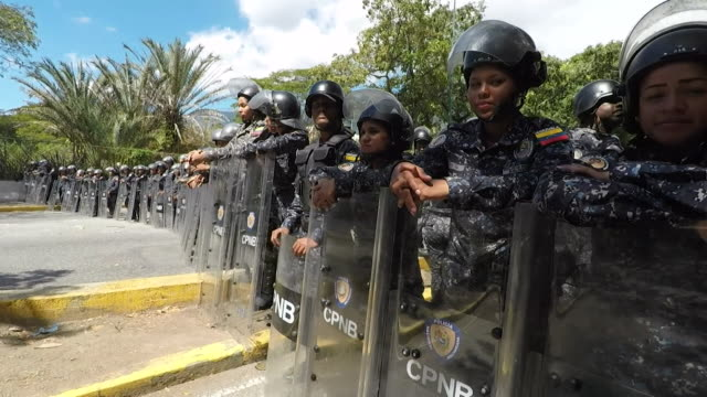 venezuelan security forces wearing riot gear standing guard at anti government protest in caracas - maduro stock videos & royalty-free footage