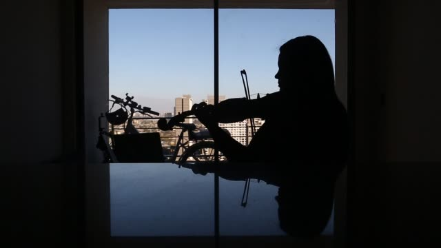 vídeos de stock, filmes e b-roll de venezuelan violinist marlly palacios, who plays in the chamber orchestra of santiago, plays the violin at her window as she gives an online lesson to... - músico