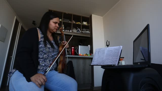 vídeos de stock e filmes b-roll de venezuelan violinist marlly palacios who plays in the chamber orchestra of santiago gives an online lesson to a music student through skype as the... - skype