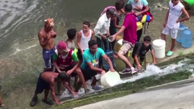 venezuelans gather on the banks of the guaire river one of the most polluted in the country to access a water pipe and fill buckets of clear water... - crisis stock videos & royalty-free footage