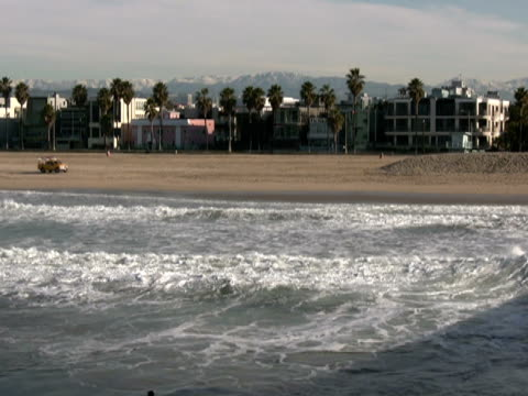 Venice Beach Winter: Snow Capped Mountains behind Surfers