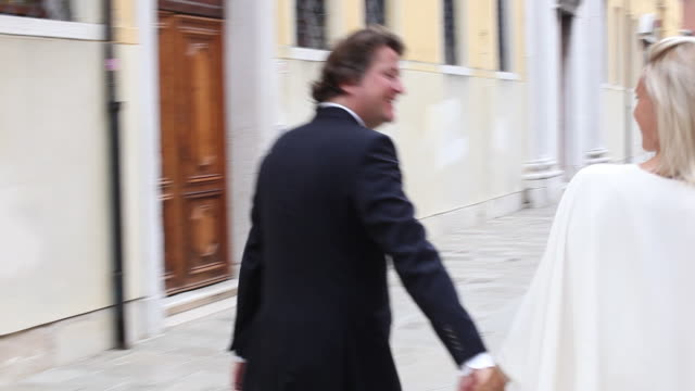 Venice, bride and groom walking down street