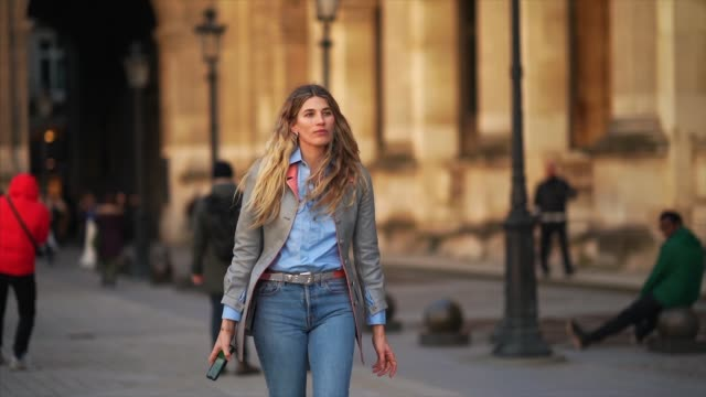 vídeos de stock, filmes e b-roll de veronika heilbrunner wears a blue shirt, a gray jacket with buttons, a belt with metallic buckle, blue denim jeans pants, outside vuitton, during... - jeans