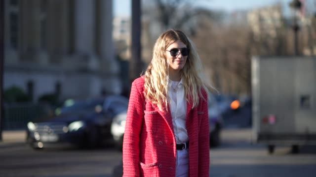 vídeos y material grabado en eventos de stock de veronika heilbrunner wears sunglasses, a white shirt, a red long tweed coat, a leather belt, white flared pants, black shoes, outside chanel, during... - camiseta
