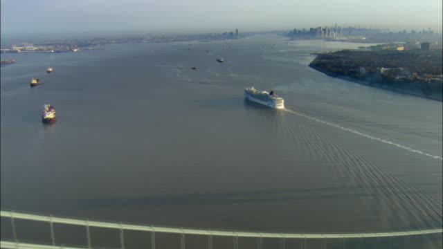 WS POV AERIAL Verrazano Narrows Bridge and cruise ship 'Norwegian Gem' with Manhattan skyline in background / New York City, New York, USA