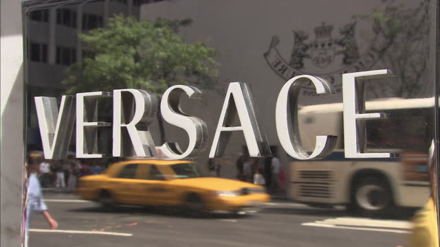 stockvideo's en b-roll-footage met cu, versace sign on window display reflecting traffic on street, new york city, new york, usa - versace modelabel