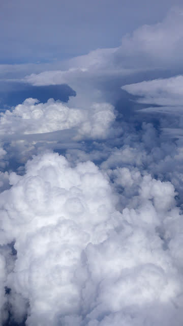 vertical 4k view of passing clouds from an airplane window - vertical stock videos & royalty-free footage