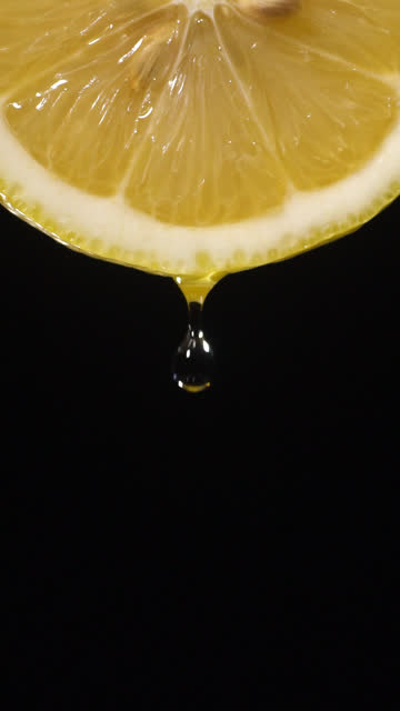 vertical and slow motion: many liquid drop from lemon slice on black - juice extractor stock videos & royalty-free footage