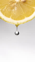 Vertical and Slow motion: Many liquid drop from lemon slice on white