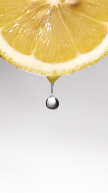 vídeos de stock e filmes b-roll de vertical and slow motion: many liquid drop from lemon slice on white - juicy