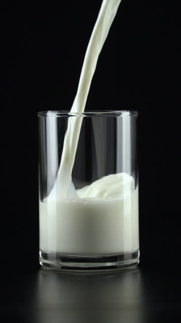 vertical and slow-motion: pouring milk into a glass on black background. - filling stock videos & royalty-free footage
