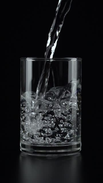 vídeos de stock e filmes b-roll de vertical and slow-motion: pouring water into a drinking glass on black background. - verter