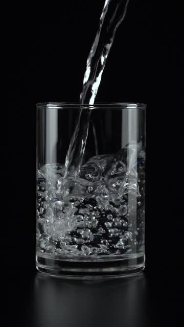 vertikale und slow-motion-bewegung: wasser in ein trinkglas auf schwarzem hintergrund gießen. - trinkglas stock-videos und b-roll-filmmaterial