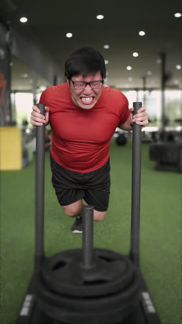 vertical asian man in red cloth training pushing prowler sled in gym - gym stock videos & royalty-free footage