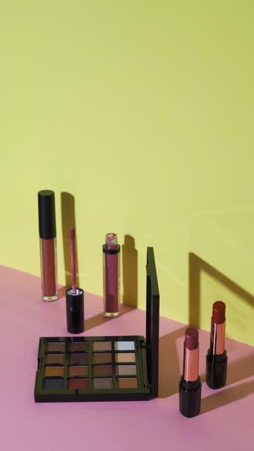 vertikal: kosmetiksammlung mit lichtmalerei auf pastellhintergrund - kosmetik stock-videos und b-roll-filmmaterial