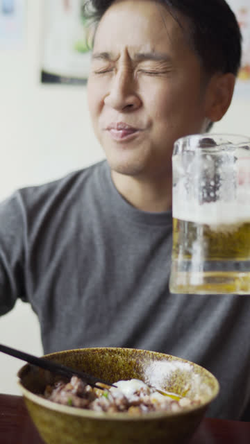 vertical enjoy eating japanese food, rice with grilled yakiniku beef and beer and  edamame - donburi stock videos and b-roll footage