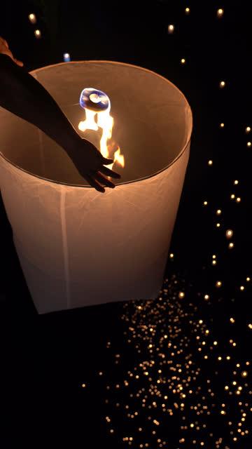 vídeos de stock e filmes b-roll de vertical hand releasing lantern to the sky in yee peng festival (yi peng) - lanterna de papel