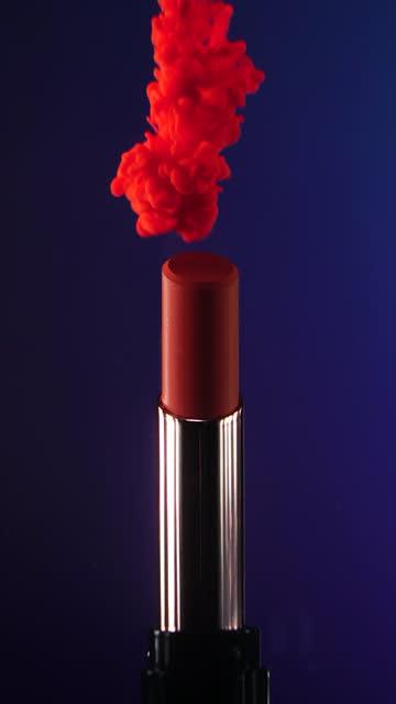 vidéos et rushes de verticale : chute d'encre tombant au rouge à lèvres avec le fond bleu foncé au mouvement lent - rouge à lèvres