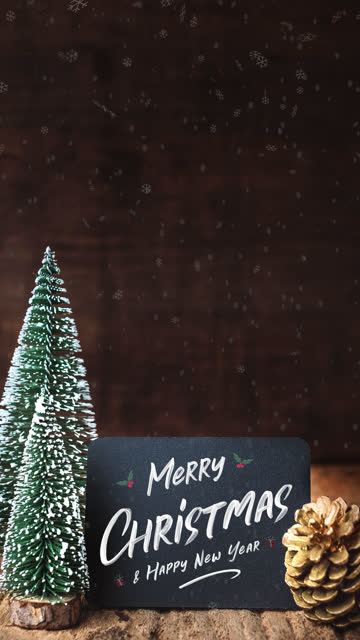 vertical merry christmas and happy new year brush stroke writing on blackboad with xmas tree and snow falling on grunge wood table and dark brown wooden wall.winter holiday greeting card - vertical stock videos & royalty-free footage