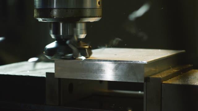 stockvideo's en b-roll-footage met een verticale frees machine snijdt door aluminium als metalen scherven vliegen door de lucht in een indoor productie-installatie - aluminium