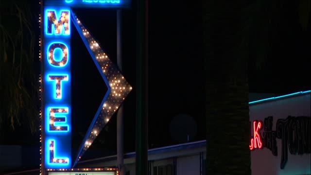 Vertical Motel sign w/ flashing lights partial building w/ satellite dish BG Reframing Palm tree BG OUT