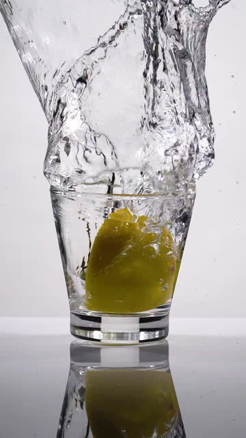 vertical shot and slow motion of lemon slice splashing into glass - vertical stock videos & royalty-free footage